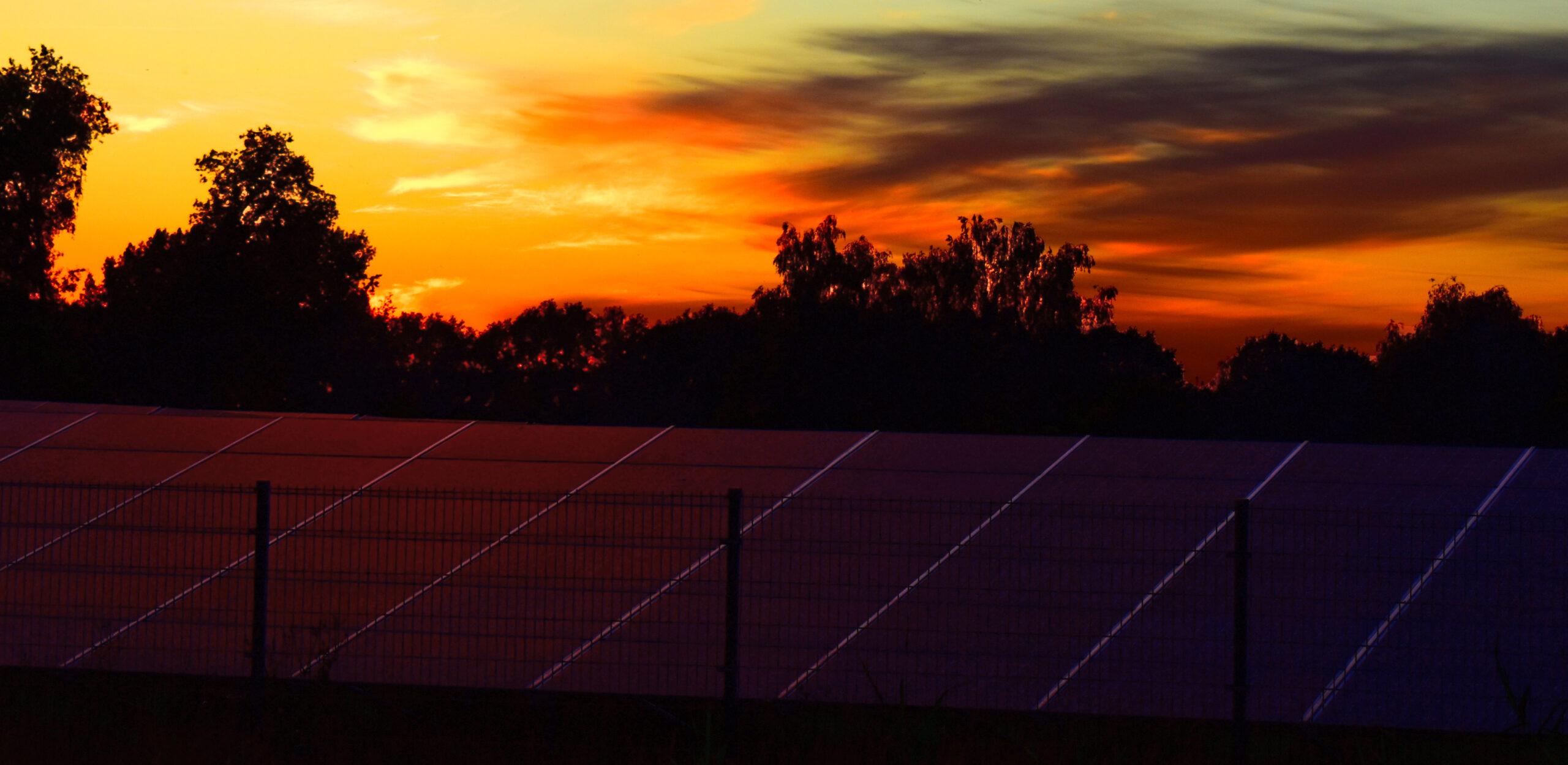 Zonnepark De Groene Weuste in Wierden tijdens zonsondergang.