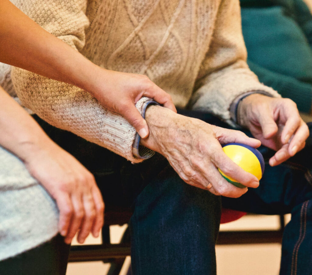 Persoon helpt een oudere met oefeningen voor de hand