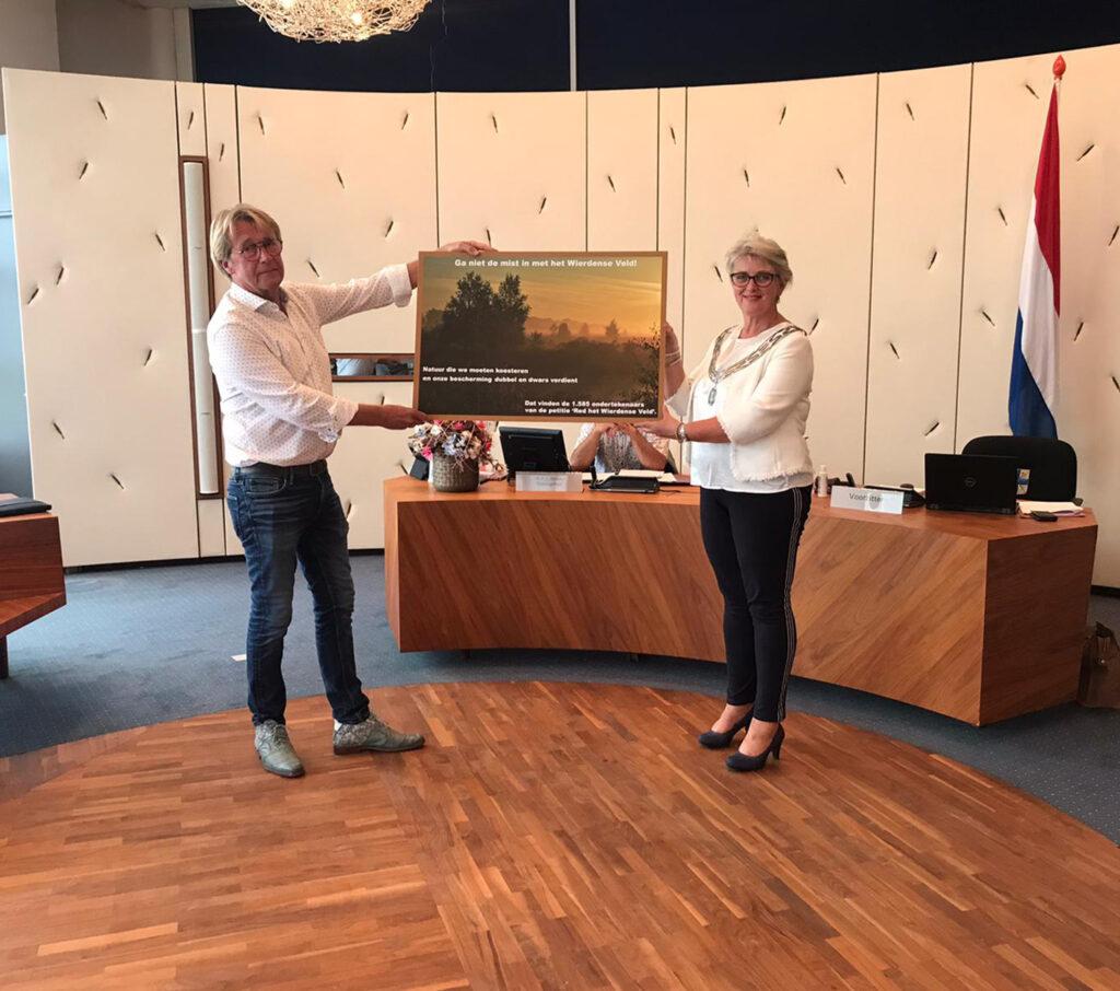 Raadslid Egbert Wessels overhandigt de petitie Red het Wierdense Veld aan burgemeester Doret Tigchelaar in de raadszaal van het gemeentehuis in de gemeente Wierden